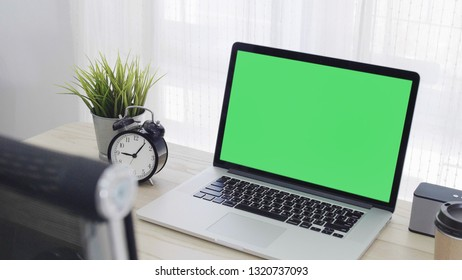 Green screen of laptop computer set on working space in cozy office, Zoom in shot
