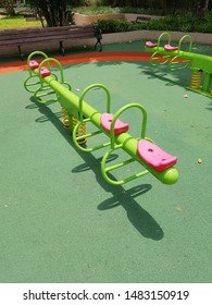 Green seesaws with pink seats in a playground