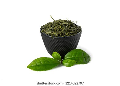 Green sencha tea in black cast iron cup with tealeaves in front isolated on white background.