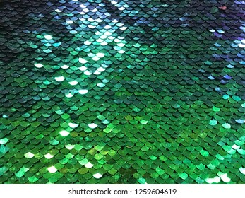 Green sequin background.