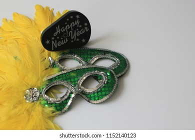 Green sequinned masquerade eye masks with yellow feathers and Happy New Year sign with white copy space on the right symbolising partying, masked balls, celebrations and hidden intrigue