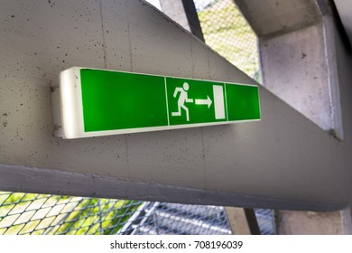 Green shining escape exit sign on white concrete wall