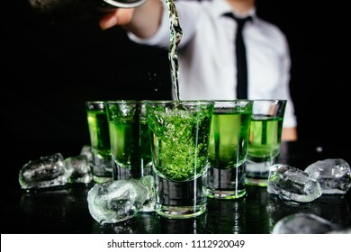 Green shots at the nightclub. Bartender pouring strong alcoholic drink into small glasses on the bar. Green cocktails at the club. Shooter cocktail.