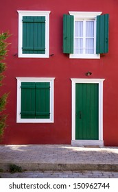 Green shutters on a red wall, in Nafplio, Greece