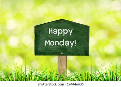 Green sign board with natural background and message Happy Monday.