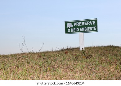 "green signboard, high in the mountain, with grassy ground and blue sky background, with the message: preserve the environment (""preserve o meio ambiente"", in portuguese)"