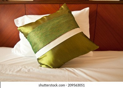 Green silk pillows on white bed
