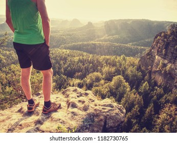 Green singlet and black pants fearless boy in rocks. Amazing view into wild nature landscape.