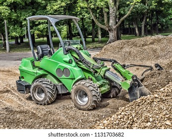Green skid loader with a load of gravel