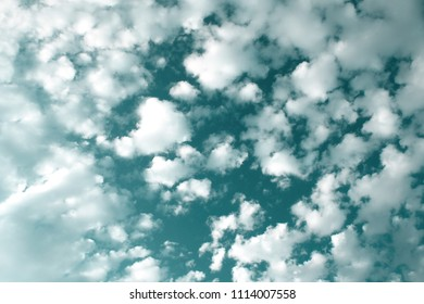 Green sky with small white clouds