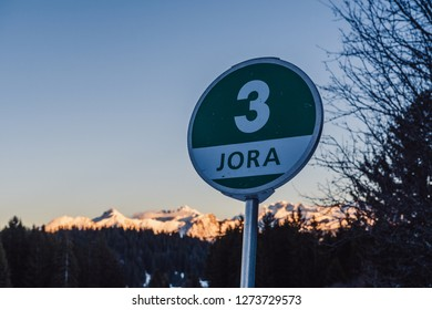 """Green slope sign for """"Jora"""" slope with sunbathed mountains in the background"""