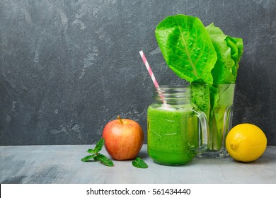 Green smoothie with apple, lettuce and lemon over dark background. Detox, dieting, vegetarian or healthy eating concept.