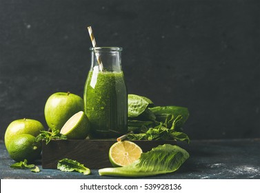 Green smoothie with apple, romaine lettuce, lime and mint, dark blue background, selective focus, copy space. Detox, dieting, clean eating, vegetarian, vegan, fitness or healthy lifestyle concept