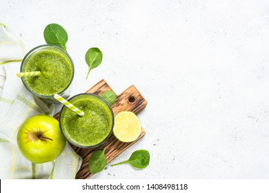 Green smoothie. Apple spinach smoothie with ingredients on white stone table. Top view with copy space.