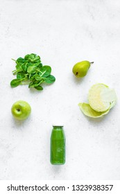 Green smoothie bottle and ingredients (apple, pear, spinach, cabbage) on white background, copy space, top view. Making detox diet vegan healthy smoothie or juice.