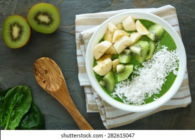 Green smoothie bowl with spinach,fresh kiwi fruit, bananas and coconut on a slate background