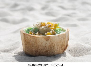 Green smoothie in the coconut bowl with mango, ice-cream and cereals