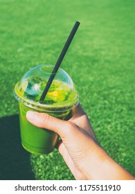 Green smoothie detox cleanse healthy eating vegan drink. Girl holding plastic cup of spinach juice at outdoor park over green grass background. Take-out breakfast POV food selfie.