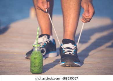 Green smoothie fitness man lacing running shoes. Athlete runner with green vegetable detox juice getting ready for morning run tying running shoe laces on wooden dock.