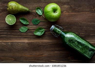 Green smoothie in glass bottle on dark, wooden background