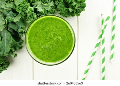 Green smoothie in a glass with kale, overhead view on white wood