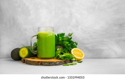 Green smoothie. Healthy green detox smoothie glass with spinach, lemon, cucumber, lemon and avocado, healthy organic food