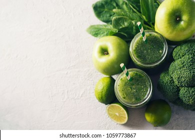 Green smoothie with ingredients, apples, lime, broccoli and spinach. Clean eating over grey texture, top view
