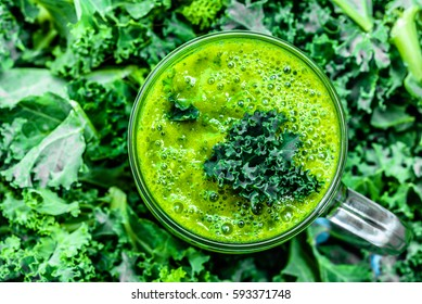 Green smoothie in jar, overhead on glass, healthy drink with vegetable leaves, background