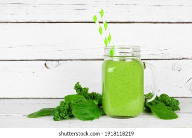Green smoothie with kale and spinach in a mason jar glass. Side view with ingredients on a white wood background.