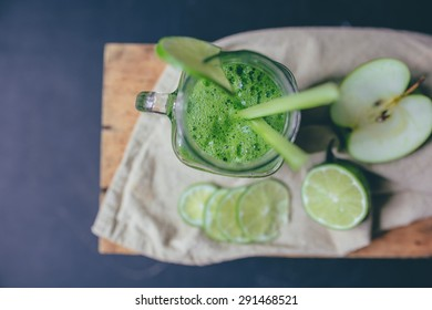 Green smoothie with lime and celery sticks