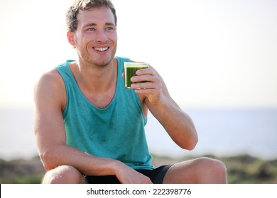 Green smoothie man drinking vegetable juice after running sport fitness training. Healthy eating lifestyle concept with young man outdoors.