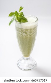 Green smoothie with mint and celery on a white background.
