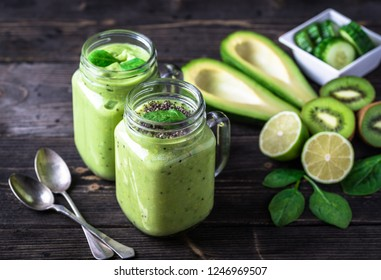 Green smoothie on dark background with avocado, spinach, lemon and kiwi on the right side.