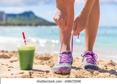 Green smoothie runner fitness woman tying running shoes at beach workout. Healthy lifestyle detox weight loss girl lacing trainers on Waikiki, Honolulu, Hawaii.