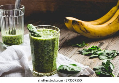green smoothie with spinach leaves, banana with peanut milk in a glass on a gray wooden background