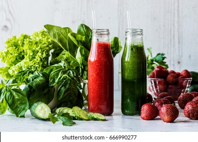 Green smoothie and strawberry smoothie in two small bottles with ingredients on a light wooden background. Healthy detox drinks.