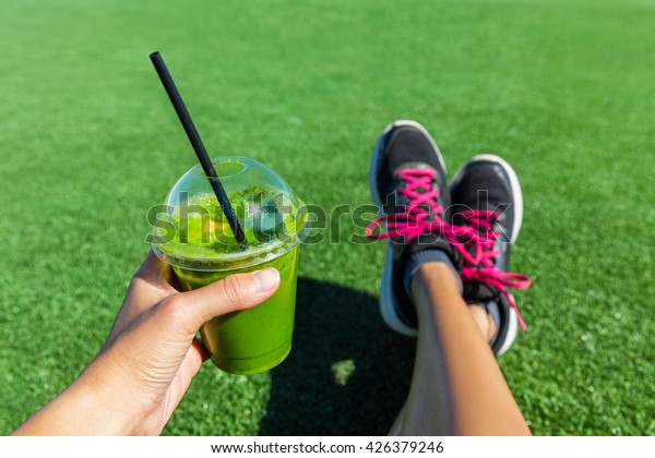 Green smoothie woman drinking plastic cup breakfast takeaway juice to go after morning run in summer park. Healthy lifestyle sporty person POV of hand holding drink with running shoes feet selfie.