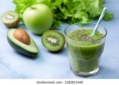 green smoothies in glass jar with fresh vegetables and herbs: broccoli, avocado, lime, celery, apple, kiwi, parsley. detox smoothies