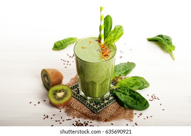 Green smoothies (healthy diet soft drink) out of the apple, kiwi, lime, spinach leaves and green tea on a white surface. Vegetarian, vegan concept