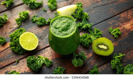 Green smoothies with kale, kiwi, apple and lime on wooden table