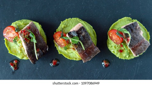 a green snack for a healthy diet. Pillow of mashed green peas with trout cooked on a steamed or oven. Excellent combination of products. Decor of microgrin with cherry tomatoes and sauce