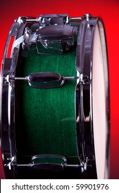 A green snare drum isolated against a redbackground in the vertical format.