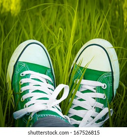 Green sneakers in the grass
