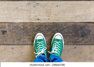 green Sneakers shoes walking on Dirty wooden top view , Canvas shoes walking on wooden