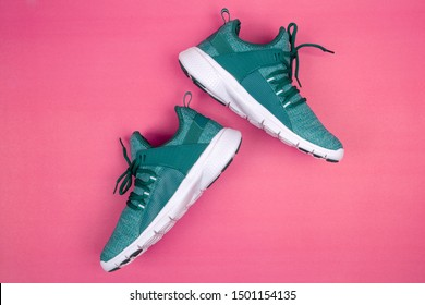 Green sneakers or sport running shoe isolated on a pink background