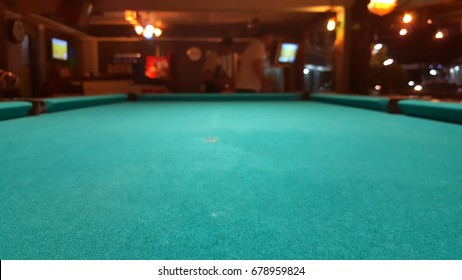 Green snooker table surface with blur and dim background in the pub.