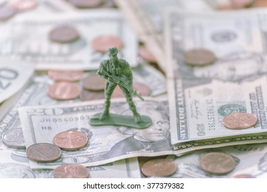 green soldier standing on heap of dollar bills and coins, protecting it by force concept.