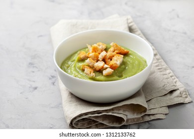 green soup with croutons in a white bowl on a gray background close-up