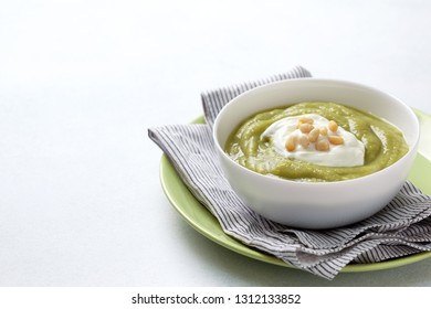 green soup with pine nuts in a white bowl on a gray background close-up