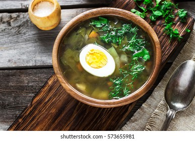 Green soup in wooden bowl. Style rustic, wooden background. Selective focus.